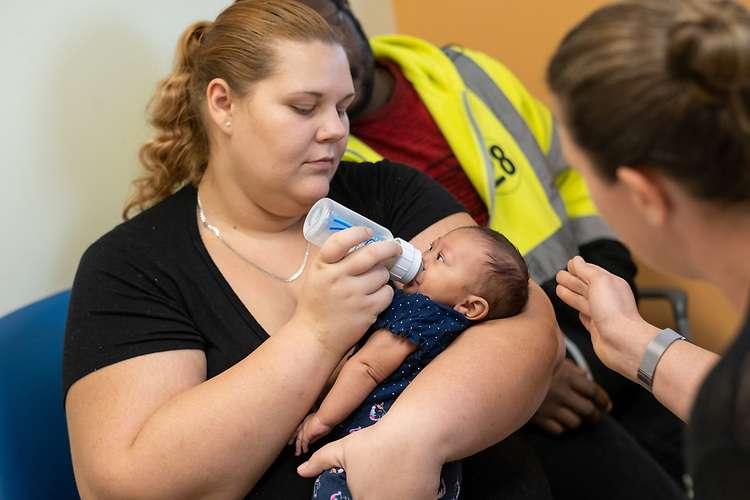 Woman bottle feeding baby